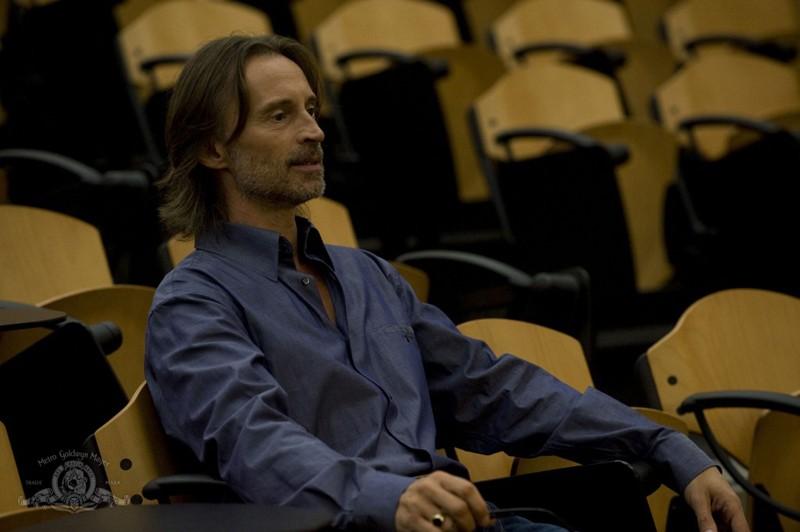 Rush (Robert Carlyle) seduto nella sua aula nell'episodio Human di Stargate Universe