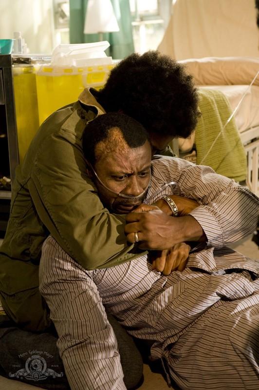 Greer (Jamil Walker Smith) abbraccia il padre (Sean Blakemore) malato nell'episodio Lost di Stargate Universe