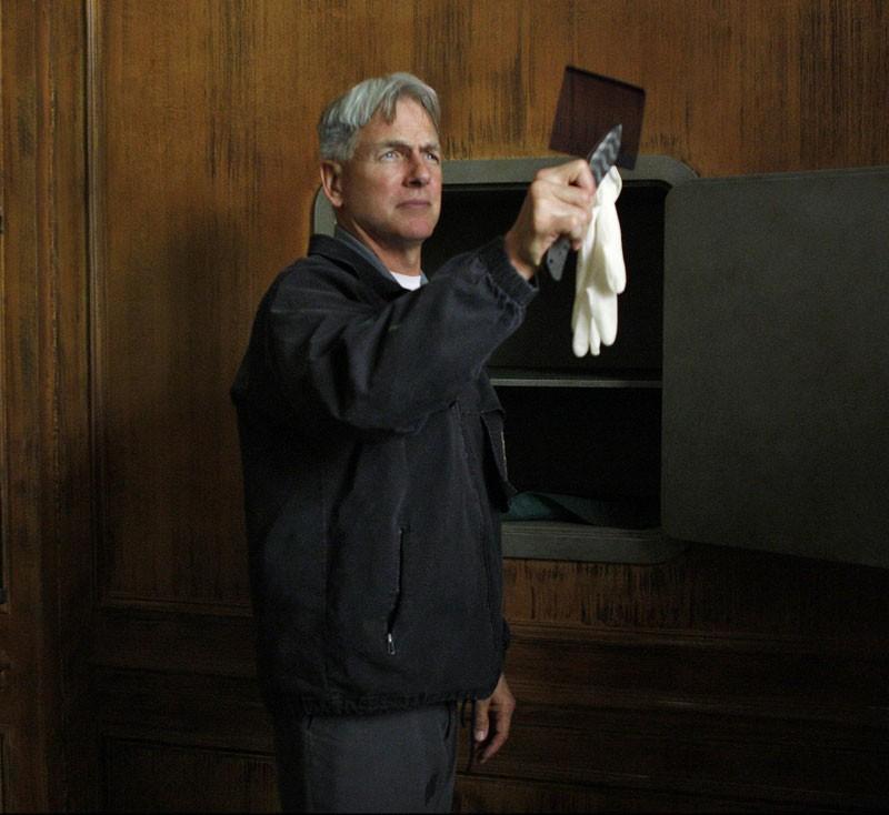 Gibbs (Mark Harmon) esamina un oggetto nell'episodio Obsession di NCIS