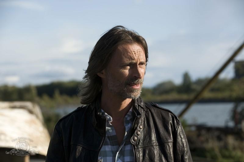 Il Dott. Rush (Robert Carlyle) sulla Terra nell'episodio Subversion di Stargate Universe