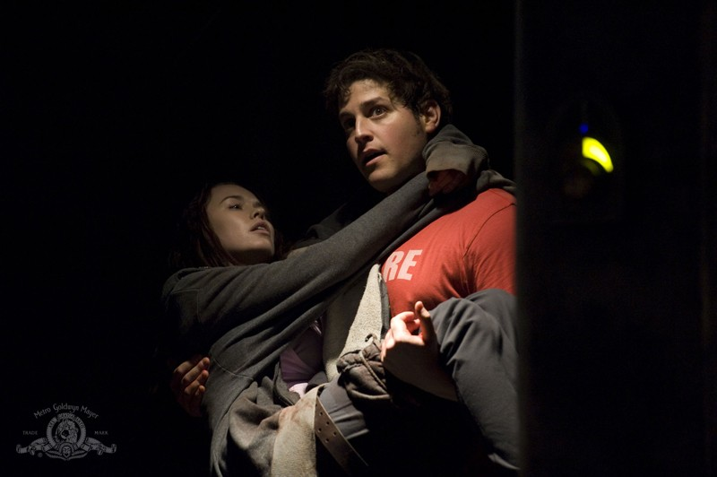 Eli (David Blue) porta in braccio Chloe (Elyse Levesque) in una scena dell'episodio Incursion: Part 2 di Stargate Universe