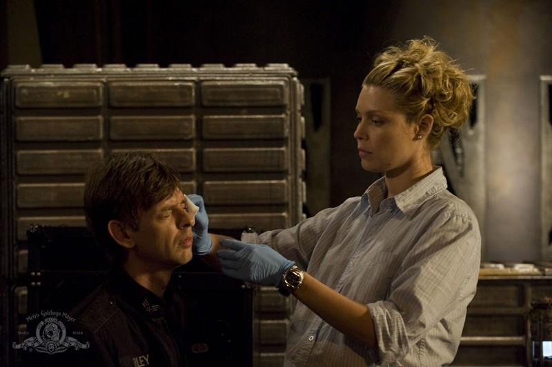 TJ (Alaina Kalanj) medica una ferita a Riley (Haig Sutherland) in una scena dell'episodio Incursion: Part 2 di Stargate Universe