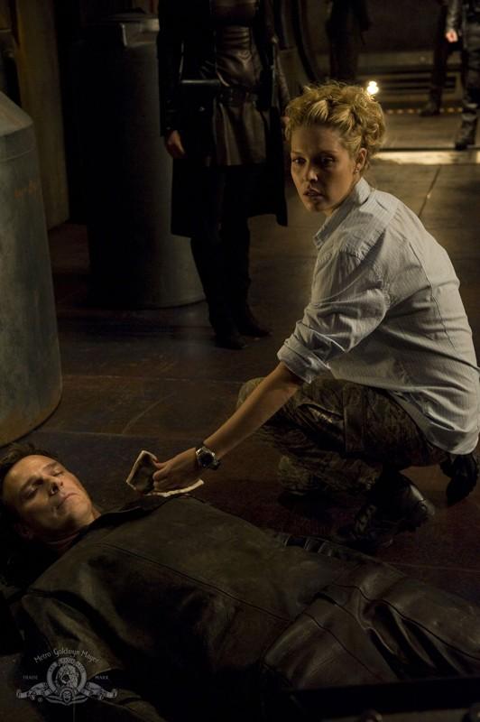 TJ (Alaina Kalanj) soccorre Varro (Mike Dopud) ferito nell'episodio Incursion: Part 1 di Stargate Universe