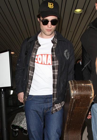 Robert Pattinson in aeroporto con la sua chitarra