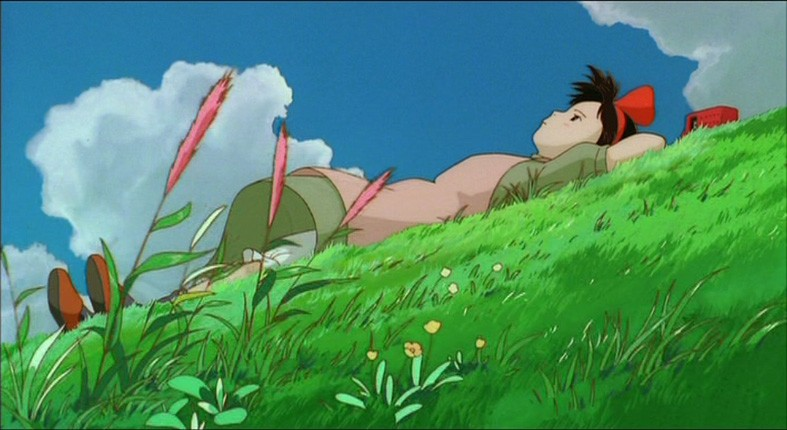 La piccola Kiki distesa su un prato in una scena del film d\'animazione Kiki consegne a domicilio