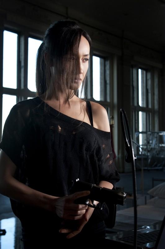 Maggie Q armata di pistola nel pilot della serie Nikita della CW