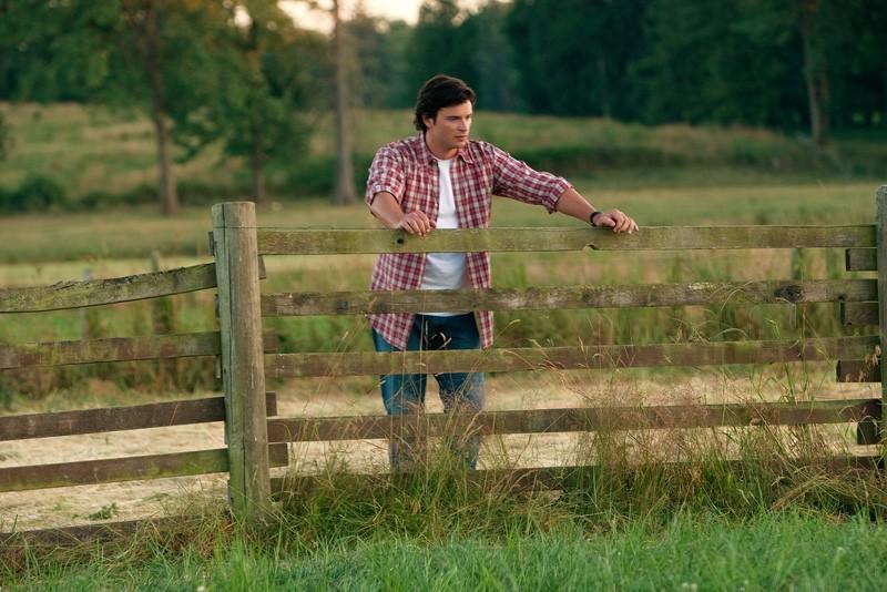 Tom Welling appoggiato alla recinzione nell'episodio Lazarus di Smallville