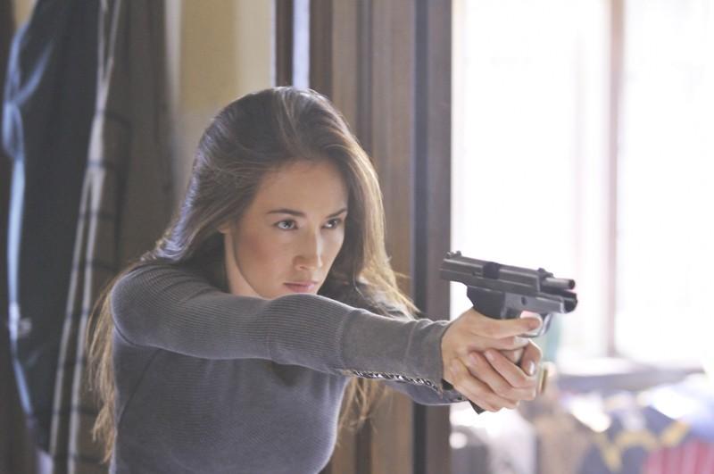 Maggie Q armata di pistola in una scena dell'episodio Kill Jill di Nikita