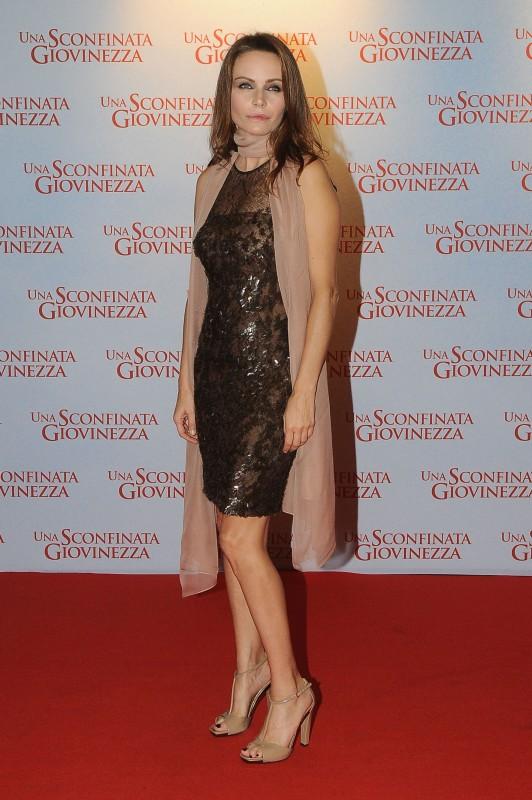 Per il red carpet di Una sconfinata giovinezza, Francesca Neri indossa un abito speciale di Gucci in pizzo marrone interamente ricamato, sandali in vernice beige e pashmina rosa cipria.