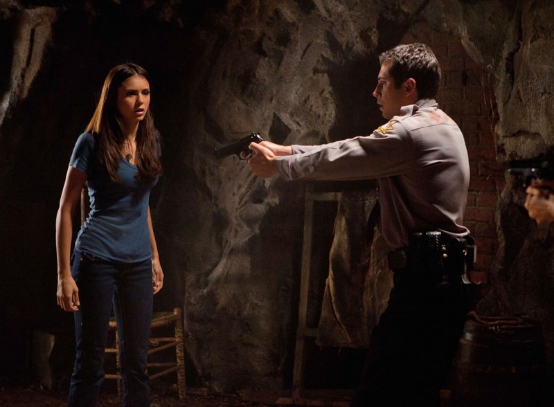 Un poliziotto punta l'arma contro Nina Dobrev nell'episodio Kill Or Be Killed di Vampire Diaries