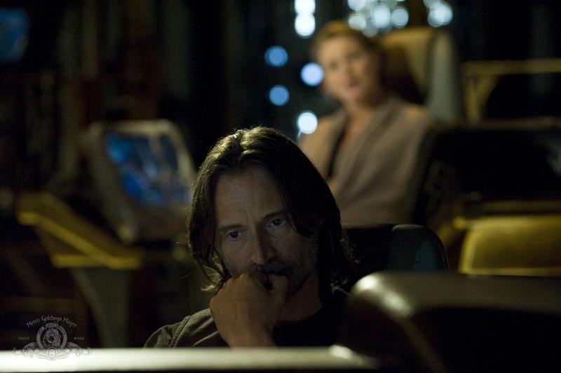 Rush (Robert Carlyle) con alle spalle Gloria (Louise Lombard) nell'episodio Aftermath di Stargate Universe