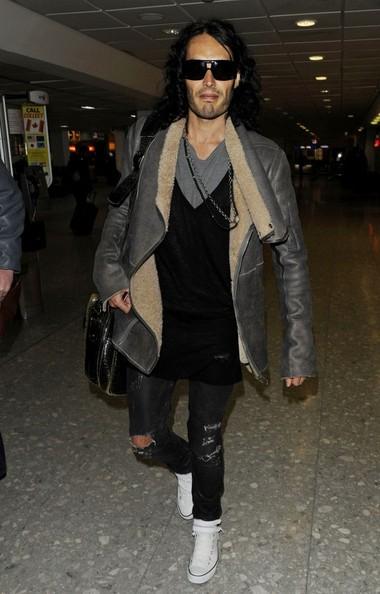 Russell Brand arriva all'aeroporto di Heathrow in una brutta giornata