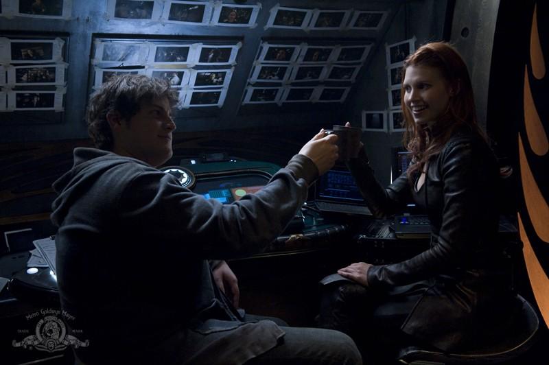 Eli (David Blue) e Ginn (Julie McNiven) brindano nell'episodio Trial and Error di Stargate Universe