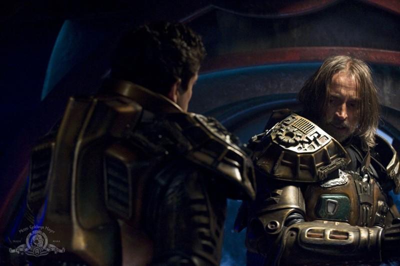 Justin Louis (di spalle) parla con Robert Carlyle nell'episodio The Greater Good di Stargate Universe
