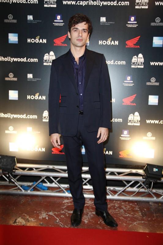 Luca Argentero presenta La donna della mia vita. L'attore indossa un abito blu notte abbinato a una camicia blu e scarpe allacciate in pelle nera (Gucci)
