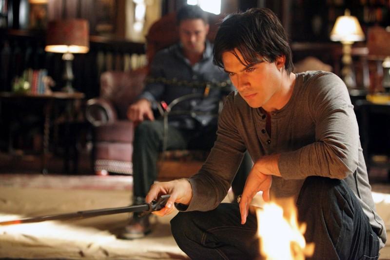 Ian Somerhalder osserva il fuoco mentre Taylor Kinney è legato a una sedia in: Plan B di Vampire Diaries