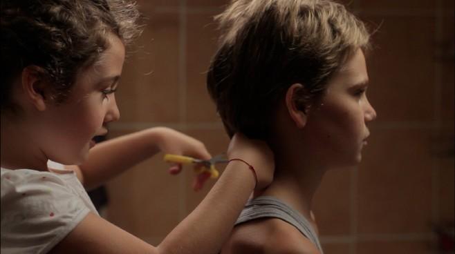 Zoe Heran si lascia tagliare i capelli da Malonn Lévana in una scena di Tomboy