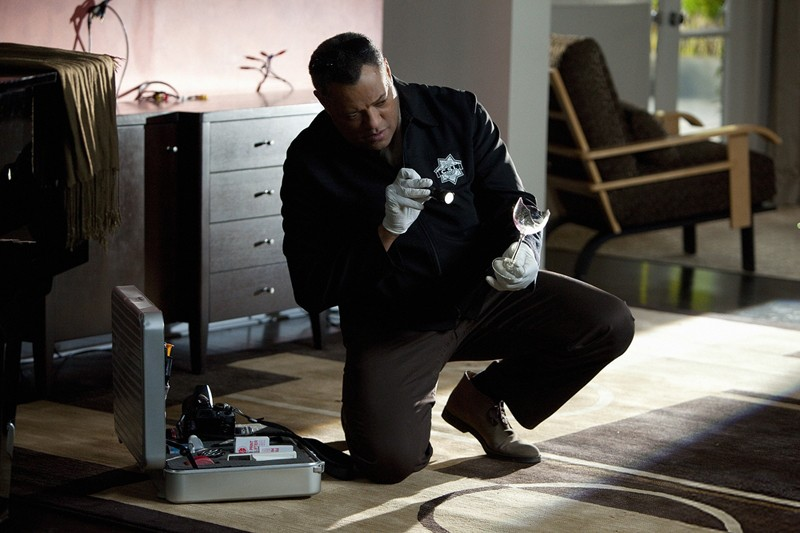 Langston (Laurence Fishburne) esamina un bicchiere nell'episodio Hitting for the Cycle di CSI: Scena del crimine