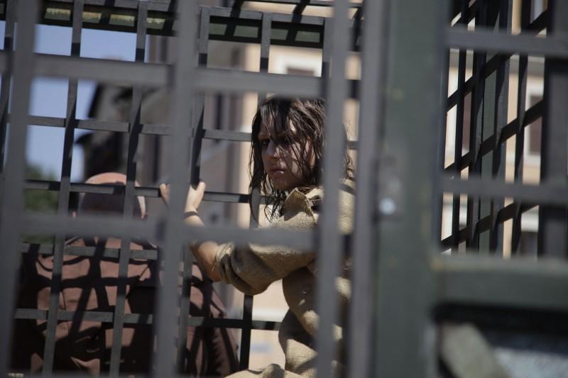 La strega scortata a Roma per il lancio del film L'ultimo dei templari chiusa in gabbia.