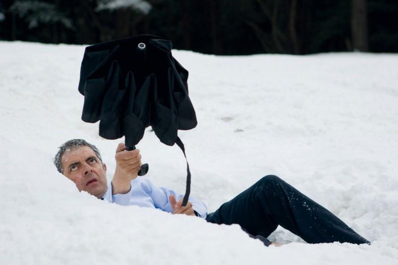 Rowan Atkinson imbraccia un ombrello tra la neve in una scena di Johnny English: La Rinascita