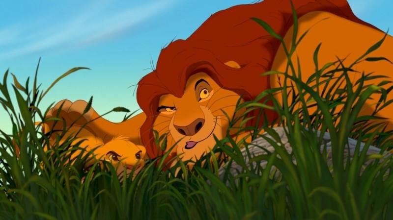 Simba insieme papà Mufasa appostato dietro a un cespuglio in una scena del film Il re leone 3D