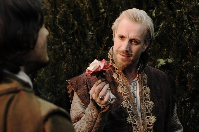 Rhys Ifans stringe tra le dita un fiore in una scena di Anonymous