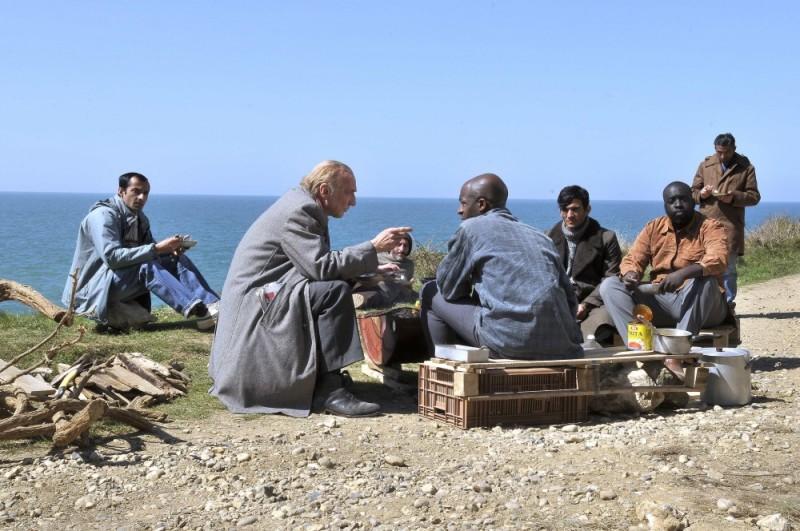 Miracolo a Le Havre: André Wilms al mare con un gruppo di stranieri in una scena del film