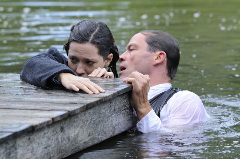 1921 - Il mistero di Rookford, Rebecca Hall e Dominic West si salvano dall'acqua aggrappandosi al molo in una scena del film