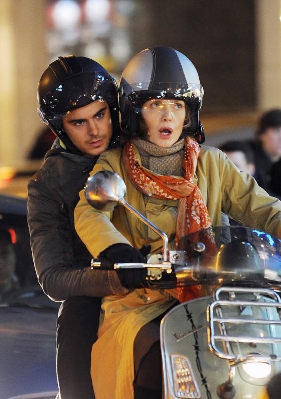 Michelle Pfeiffer e Zac Efron nel traffico su un motorino in una scena di Capodanno a New York