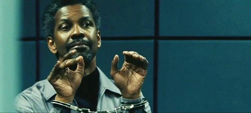 Denzel Washington sogghigna in manette una scena del thriller Safe House