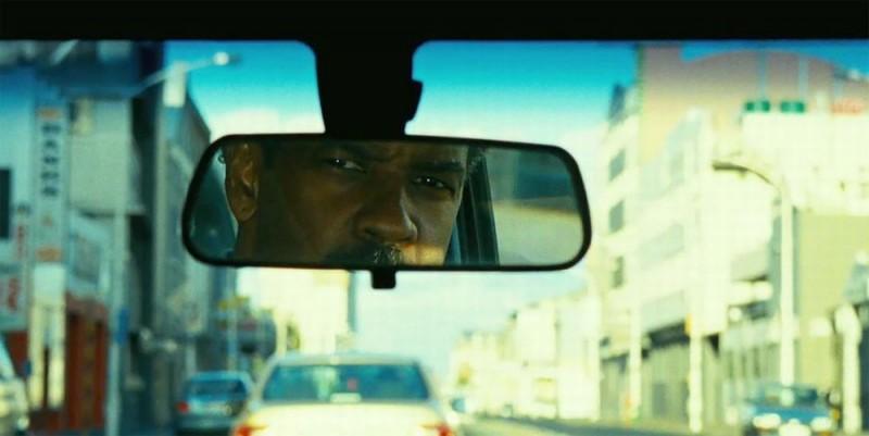 Safe House: Denzel Washington si riflette nello specchietto retrovisore in una scena del film