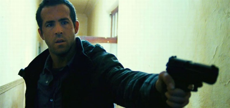 Safe House: Ryan Reynolds impugna la sua pistola in una scena del film
