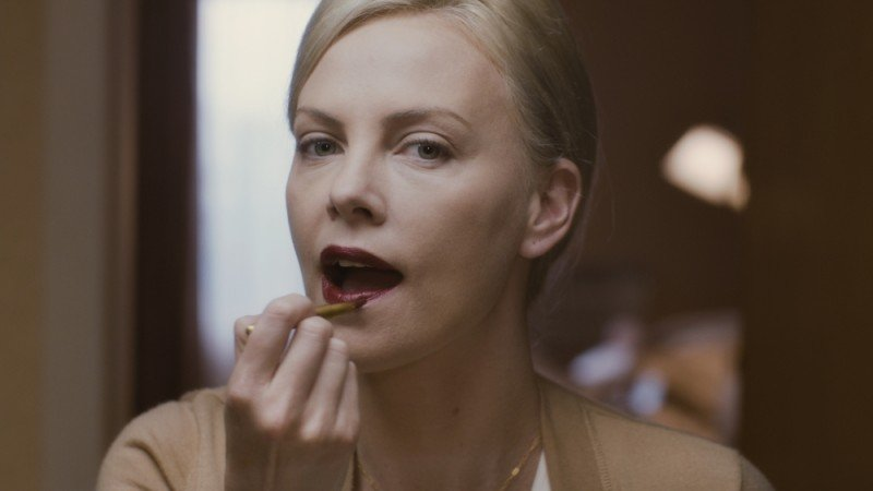 Charlize Theron si tinge le labbra in una scena del film Young Adult