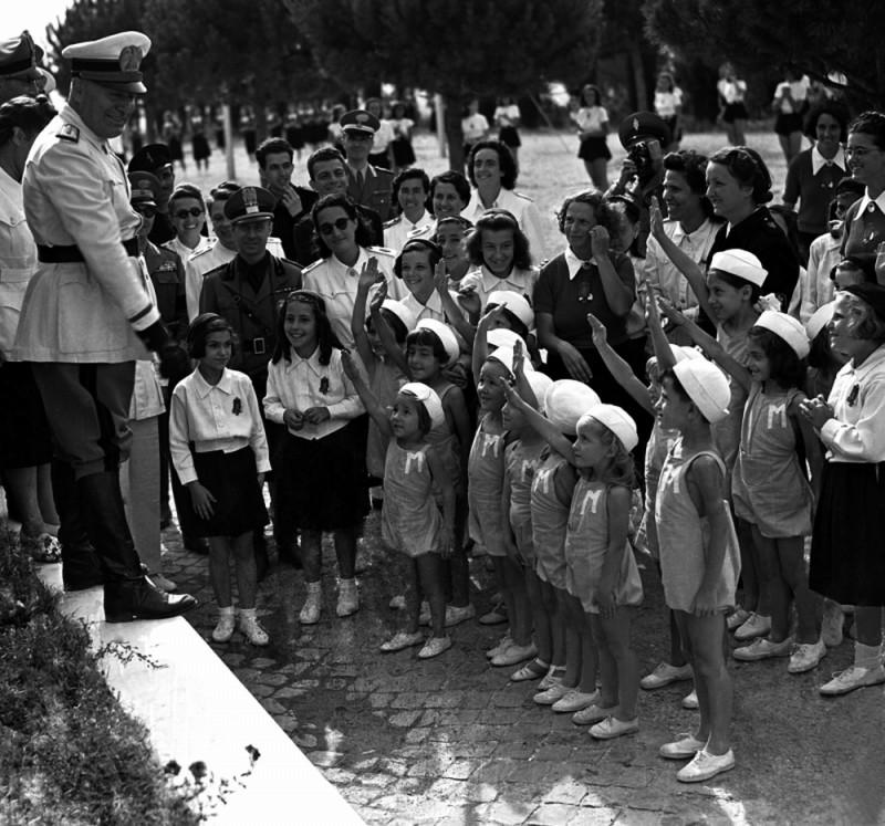 Il sorriso del capo: Benito Mussolini in un'immagine d'archivio circondato da un gruppo di bambini