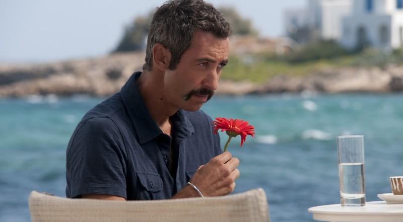 Paolo Kessisoglu annusa un fiore rosso in una scena di Immaturi - Il viaggio