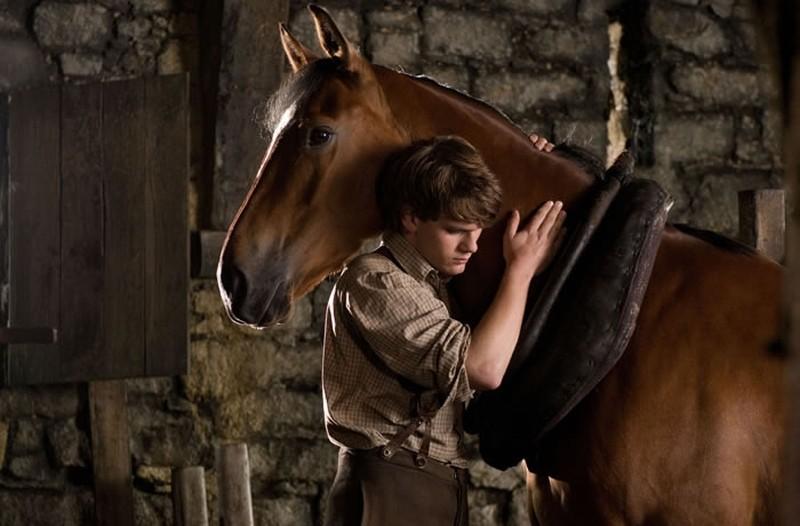 Jeremy Irvine abbraccia il suo cavallo in una scena di War Horse