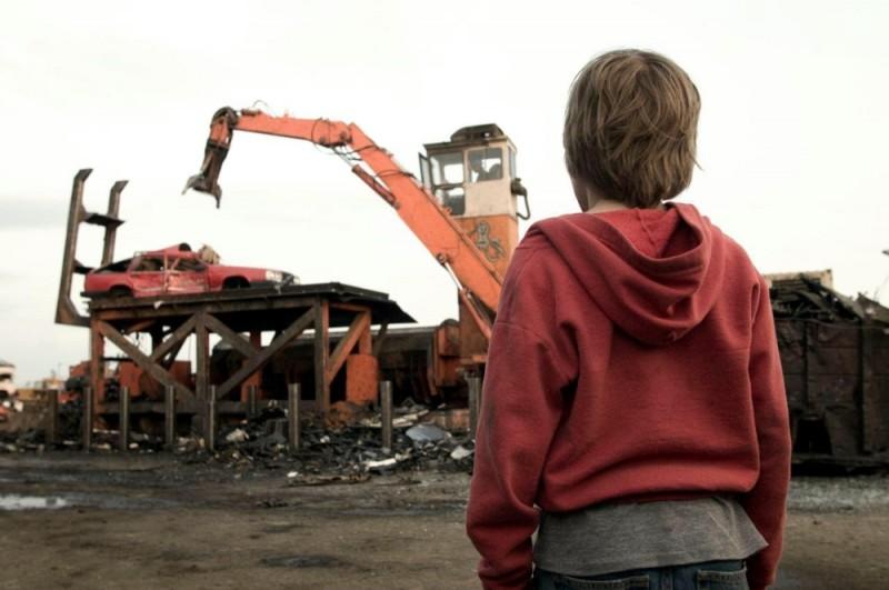 Hesher è stato qui: Devin Brochu di spalle assiste alla demolizione di un'auto in una scena del film