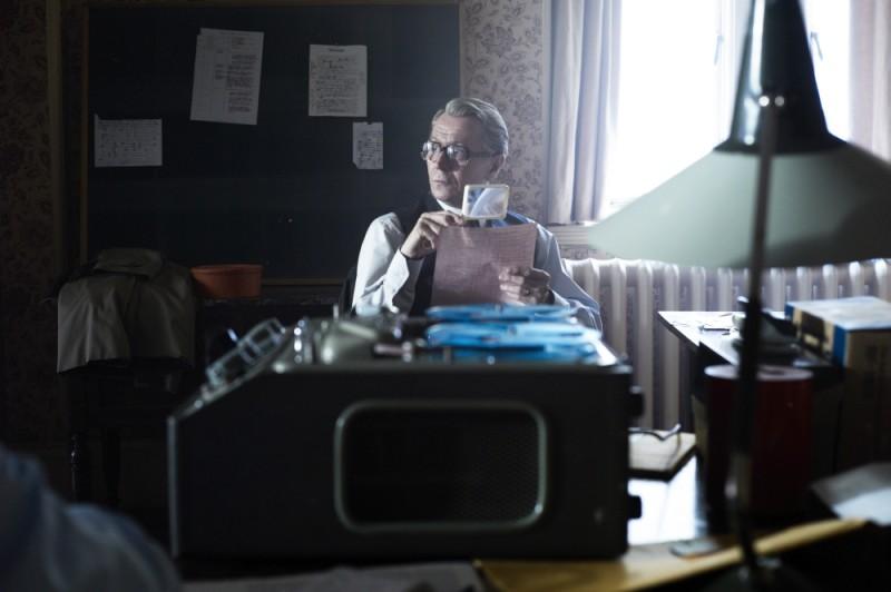 La talpa: Gary Oldman studia delle carte con la lente d'ingrandimento in una scena del film