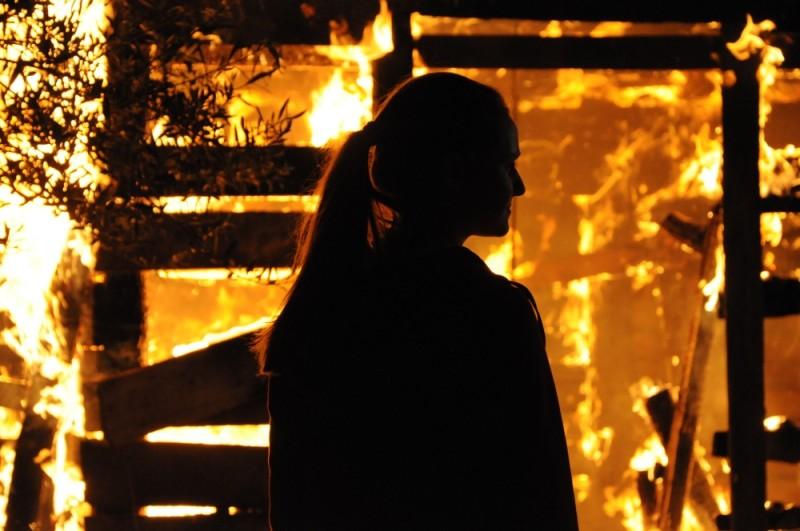 Sindi Laçej di spalle davanti alle fiamme in una scena del dramma La faida
