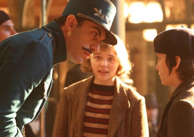 Asa Butterfield insieme a Sacha Baron Cohen e Chloe Moretz in una scena di Hugo Cabret 3D