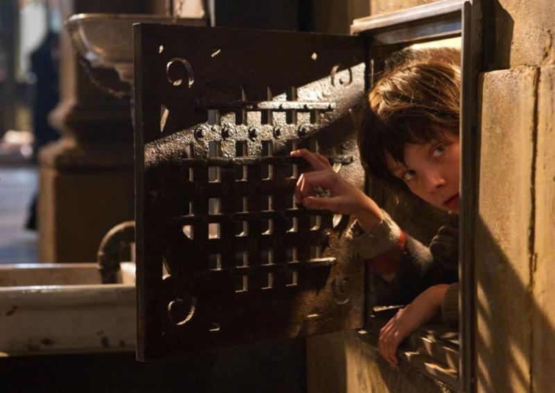 Hugo Cabret 3D: Asa Butterfield fa capolino da un passaggio segreto in una scena del film