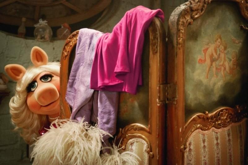 Miss Piggy fa capolino dietro il separé in un'immagine de I Muppet