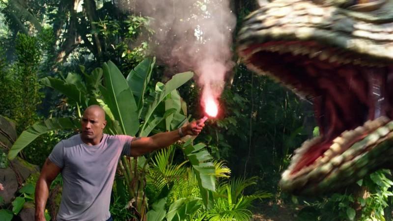 Dwayne Johnson si difende da un dinosauro in una scena del film Viaggio nell'isola misteriosa