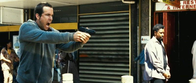 Ryan Reynolds in una scena del thriller Safe House - Nessuno è al sicuro insieme a Denzel Washington