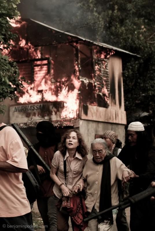 Captive, Isabelle Huppert in una drammatica scena del film fugge da un incendio insieme a Rustica Carpio