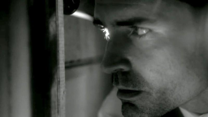 Jason Patric spia dal buco di una serratura in una scena del thriller Keyhole
