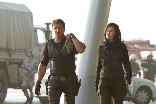 Sylvester Stallone e Yu Nan camminano fianco a fiano in una scena di in The Expendables 2
