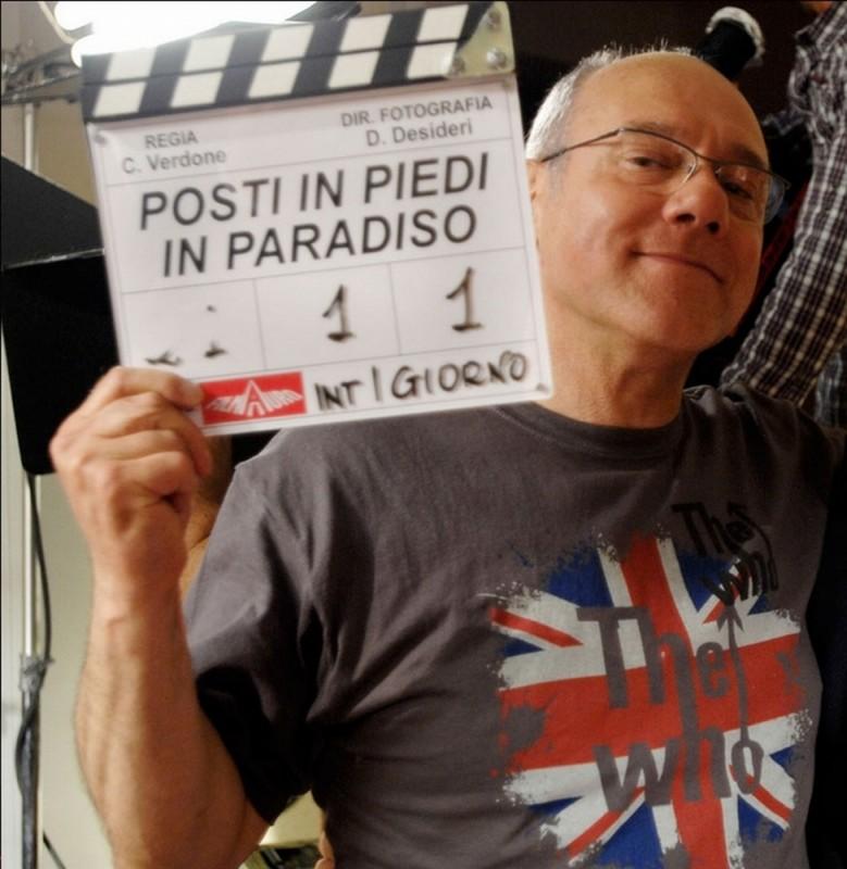 Carlo Verdone sul set di Posti in piedi in Paradiso mostra con orgoglio il ciak