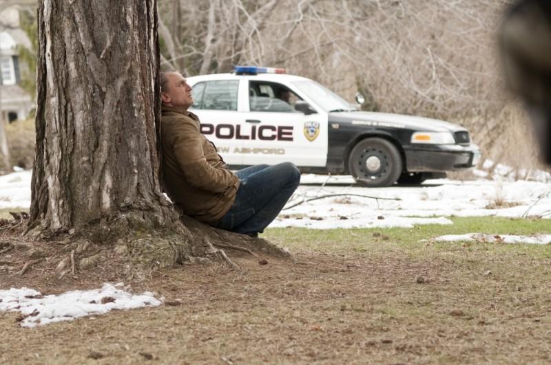 Daniel Craig rannicchiato sotto un albero in un'immagine di Dream House