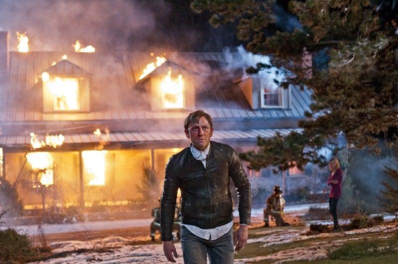 Daniel Craig si allontana dalla sua casa in fiamme in una scena di Dream House